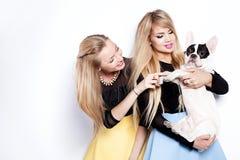 Amies heureuses avec le chien Image stock