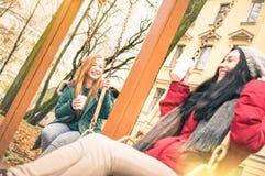 Amies heureuses ayant l'amusement sur le jeu d'oscillation au parc en automne Photo stock