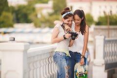 Amies heureuses dans la ville avec l'appareil-photo Photo libre de droits
