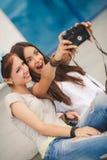 Amies heureuses dans la ville avec l'appareil-photo Images libres de droits