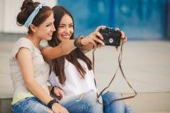 Amies heureuses dans la ville avec l'appareil-photo Image stock