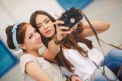 Amies heureuses dans la ville avec l'appareil-photo Image libre de droits