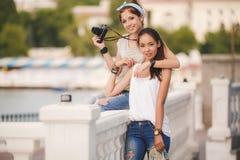 Amies heureuses dans la ville avec l'appareil-photo Photographie stock