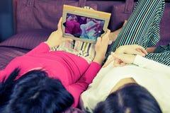 Amies heureuses dans le lit prenant le selfie avec le comprimé drôle Image libre de droits
