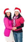Amies heureuses de femmes avec des chapeaux de Santa Image stock