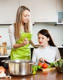 Amies heureuses faisant cuire la soupe ensemble Photographie stock libre de droits