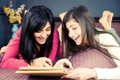 Amies heureuses jouant avec le comprimé dans le lit Photographie stock libre de droits