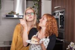 Amies heureuses mangeant le gâteau dans la cuisine Image stock
