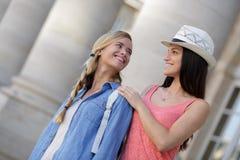 Amies heureuses marchant par la ville pendant des vacances Photographie stock