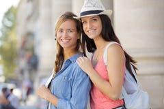 Amies heureuses marchant par la ville pendant des vacances Images libres de droits