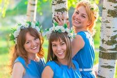 Amies heureuses posant près du bouleau Image libre de droits