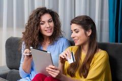 Amies heureuses s'asseyant dans le divan faisant l'achat en ligne Images libres de droits