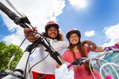 Amies heureuses se tenant avec leurs bicyclettes Image stock
