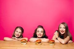 Amies heureuses souriant à la table avec des hamburgers Image libre de droits