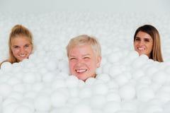 Amies heureuses support adulte de mère de portrait et de fille entouré par les boules en plastique blanches Photographie stock