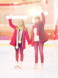 Amies heureux ondulant des mains sur la piste de patinage Photo stock