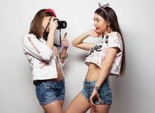 Amies heureux prenant quelques photos avec l'appareil-photo, au-dessus du fond blanc Photo libre de droits