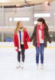 Amies heureux sur la piste de patinage Photographie stock libre de droits