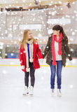 Amies heureux sur la piste de patinage Photos libres de droits