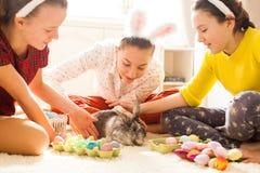 Amies jouant avec le lapin Photos stock