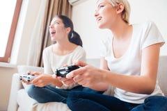Amies jouant des jeux vidéo Photographie stock libre de droits