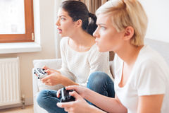Amies jouant des jeux vidéo Image libre de droits