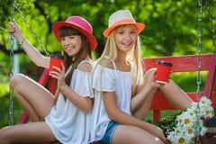 Amies joyeuses ayant l'amusement sur l'oscillation extérieure Concept d'amitié Photographie stock libre de droits
