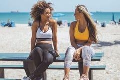 Amies Lounging dans les vêtements de sport sur la plage Photo libre de droits