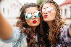 Amies magnifiques de brune avec la coiffure, les lunettes de soleil reflétées et les lèvres rouges faisant le selfie avec le visa Photos libres de droits