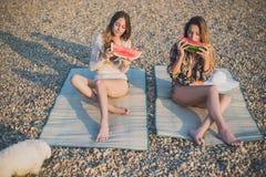 Amies mangeant la pastèque sur la plage Photographie stock libre de droits