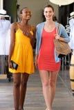Amies marchant dans un sourire de centre commercial Photos libres de droits