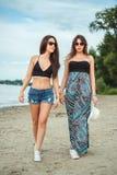Amies marchant sur la plage et parler Photo libre de droits