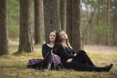 Amies mignons s'asseyant dans la marche de forêt Photos libres de droits