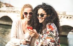 Amies multiraciales heureuses ayant des outddors d'amusement avec le téléphone portable Photographie stock