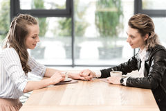 Amies occasionnelles s'asseyant au café et tenant des mains tout en buvant du café Image stock