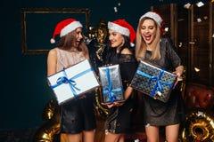 Amies ouvrant des cadeaux de Noël ensemble Photos libres de droits