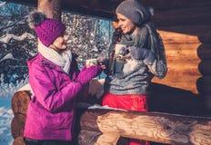 Amies passant des vacances d'hiver sur le cottage de montagne Images stock