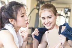 Amies prenant le selfie sur le mobile dans le gymnase de forme physique Photographie stock
