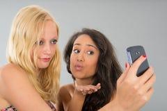 Amies prenant le selfie tout en embrassant Images libres de droits
