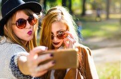 Amies prenant un selfie en parc Photos libres de droits