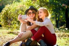 Amies prenant un selfie en parc Images libres de droits