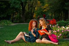 Amies s'asseyant sur l'herbe en parc Photos stock