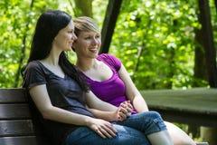 Amies s'asseyant sur le banc de parc tenant des mains, horizontales Photos stock