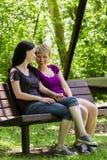 Amies s'asseyant sur le banc de parc tenant des mains, verticales Image stock
