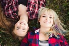 Amies se couchant tête à tête sur une herbe photos libres de droits