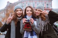 Amies se tenant avec l'appareil-photo de photo dehors Images stock