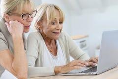 Amies supérieures de femmes ensemble sur l'ordinateur portable Photo libre de droits