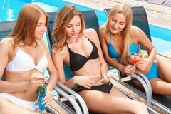 Amies sur la chaise longue près de la piscine Images stock