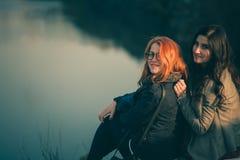 Amies sur le rivage du lac au coucher du soleil Amie heureux étreignant dans une forêt au coucher du soleil Photo stock