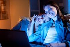 Amies sur un sofa avec l'ordinateur portable Image stock